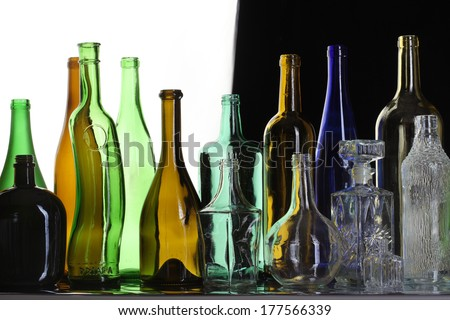close-up collection of beautiful colored bottles of different shapes studio on black and white background