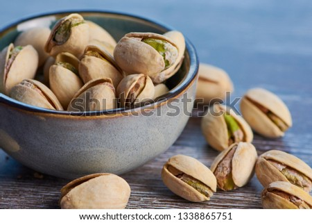 close up color picture of pistachios roasted and salted in a ceramic bowl on a wooden surface