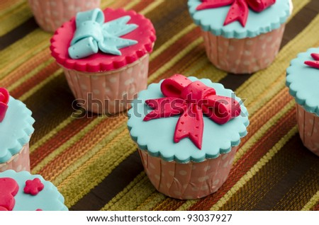 Close up colorful cup cakes on cotton background