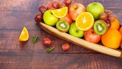 close up colorful fresh fruit orange apple grape kiwi fruit full of vitamin c on wooden table