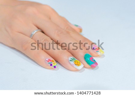 close up colorful gel nail art on fashionista woman fingernail painting beautiful flamingo,hibiscus flower,mix fruit fresh and green coconut tree design for summer