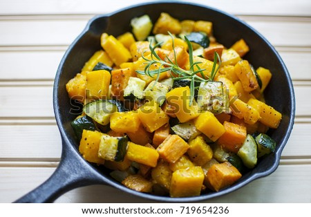 Close up colorful roasted rosemary butternut squash sweet potato and zucchini garnished with fresh rosemary in cast iron pan on wood background