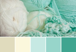 Close up colorful yarn texture background, light mint green and creamy beige strains. Shallow depth of focus. Color palette swatches, fresh trendy combination of colors for styling, pastel nuances.