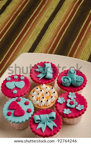 Close up colorfull cup cake on white plate on nice mat color