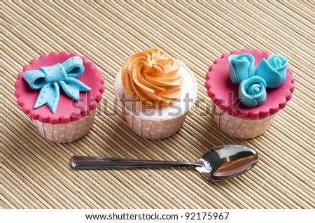 Close up colorfull cup cake with spoon on bamboo mat