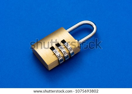 Close-up combination golden padlock on the blue background. #1075693802