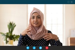 Close up computer screen web camera view beautiful young indian arabic businesswoman involved in video call conversation negotiation or passing online job interview, distant communication concept.