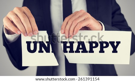 Close up Conceptual Businessman Tearing a White Paper with Unhappy - Happy Message Isolated on a Gray Background, Toned Retro Effect.