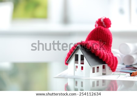 Close up Conceptual of Insulation Symbol House with Red Bonnet in office burreau.