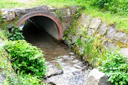 close-up concrete semicircular arch of a water drain well, a stream flows into a canal, sewage drains, the concept of a drainage system in Europe, a river drainage