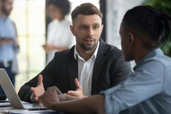 Close up confident businessman talking with african american businessman in boardroom at meeting. Leader presenting new business concept for diverse male colleague discuss. Team together using laptop.