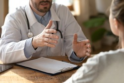 Close up confident young male doctor physician gesturing, explaining disease treatment results or examining ill focused female patient at checkup clinic meeting, professional medical consultation.