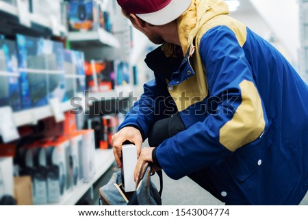 Photo of  close up consumer  thief's hands putting the new gadget in the pocket in the store