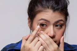 close up contact lens on woman finger.