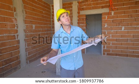 CLOSE UP: Content male architect smiles as he looks around the empty room while holding his plans to the modern house under construction. Caucasian Man smiles while looking around unfinished house. stock photo