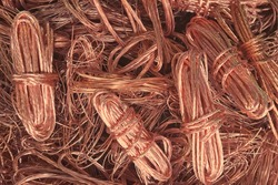 Close up copper wire scrap metal for recycliing or reproducing in the melting foundry. Bright berry copper raw material are reused in the industry. Non-ferrous scrap in the waste recycle manufacture.