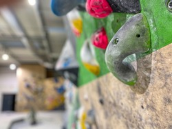 CLOSE UP. COPY SPACE, DOF: Detailed shot of an artificial climbing wall at a training center closed due to covid 19 restrictions. Bouldering hall remains empty during the global coronavirus lockdown.