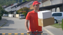 CLOSE UP, COPY SPACE, DOF: Smiling young courier rides his e-scooter down empty suburban street with two packages. Parcel delivery man holds two boxes in one hand while riding an electric scooter.