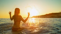 CLOSE UP, COPY SPACE, LENS FLARE: Surfer girl sitting on her surfboard and splashing water as she waits at the line up at picturesque sunrise. Fit woman on surfing trip waiting for her first wave.