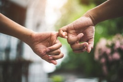 Close up couple holding pinkies fingers  in park in autumn as swear and promise gesture in wedding ceremony. Hands holding of love Valentines day theme. Togetherness of friendship with green natural