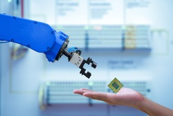 Close-up CPU chipset processor on hand human for sending to automation robot for upgrade efficiency to work on smart factory, blue tone color background, industry industry 4.0 concept