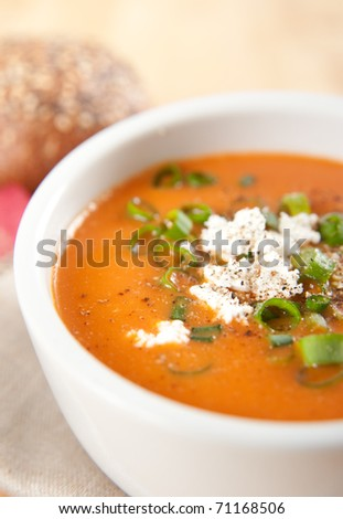 Close Up Creamy Bell Pepper and Tomato  Soup Garnished with Goat Cheese, Green Onion and Pepper