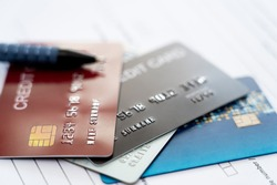 Close up credit cards on insurance document for payment of Annual insurance expenses that must be paid regularly instead of using cash