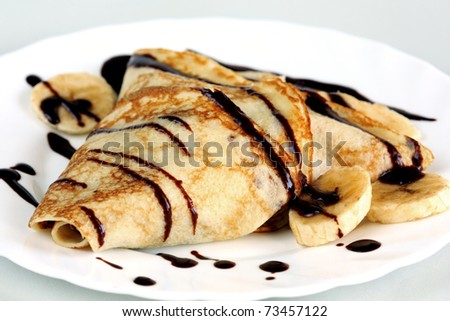 close-up crepe with bananas and chocolate on white plate