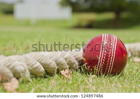 Close up Cricket ball on field touching boundary rope four runs with copy space