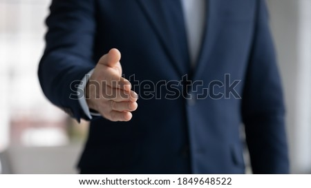 Close up crop image young businessman reaching out hand for shaking, proposing good deal to partner, making greeting gesture to client, welcoming new employee at work, congratulating with achievement. Stockfoto ©