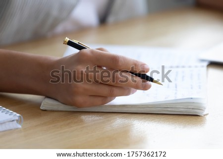 Close up crop view of woman hold pen writing making notes in notebook studying at home, female handwrite in exercise book, take educational course or training, seminar, education concept