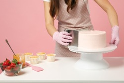 Close up cropped chef cook confectioner or baker in white t-shirt cooking at table isolated on pink pastel background in studio. Cream application cake making process. Mock up copy space food concept