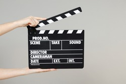 Close up cropped female holding in hand classic director clear empty black film making clapperboard isolated on grey background. Cinematography production concept. Copy space for advertising mock up