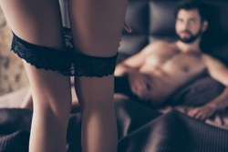 Close up cropped focused photo of young sexy bearded brunet lying on the bed, his lover is taking of her black panties, so tempting and seductive, provocative and horny