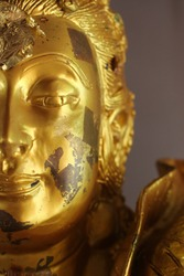 Close-up cropped half face of a golden Buddha statue in a temple in southeast Asia.