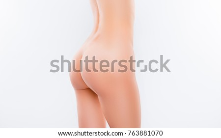 Close up cropped half turned photo of perfect sexy slim woman's body and tightened naked bottom, isolated on white background