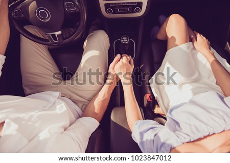 Close up cropped high angle shot of driver husband, lady wife, holding each others arms, on their way to dreams and happiness, highway, honeymoon, feelings, married family, friendship, destination