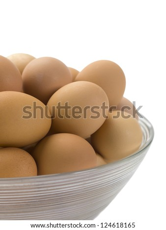 Close-up cropped image of a clear bowl with brown eggs over the white background