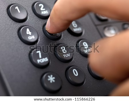 Close-up cropped image of a person dialing landlines phone.