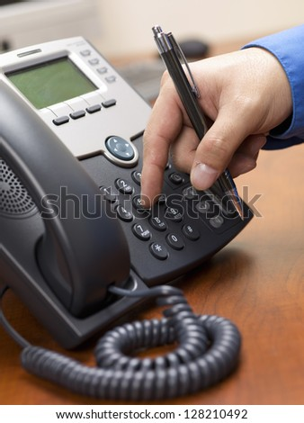 Close-up cropped image of a person dialing number on modern land line phone.