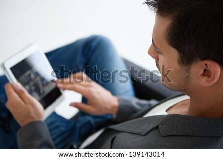Close up cropped image of an Attractive business man in his 20s working on think pad - stock photo