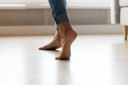 Close up cropped image of barefoot girl in blue jeans standing on electric heated floor at home. Young woman stands on tiptoe, enjoy walking without room slippers on clean floor or dancing.