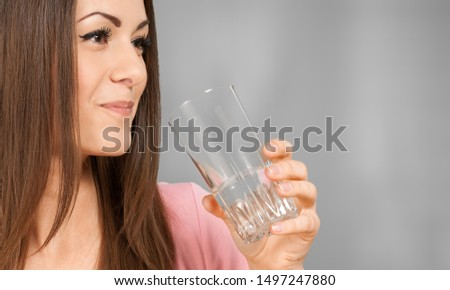 Close up cropped image thirsty woman holding glass drinks still water preventing dehydration, helps maintain normal bowel function and balance of body, skin and health care, healthy lifestyle concept