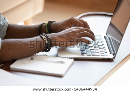 Close up cropped image young black man using laptop at home, remotely working, distantly studying in online university, writing mail, web surfing information, passing test, upgrading knowledges.