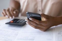 Close up cropped of African American woman using smartphone, calculating bills, browsing online banking service, checking balance, analyzing financial documents, managing planning household budget