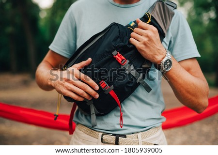 Close up cropped photo of a waist bag for travel on the shoulder of a young man in the woods. Equipment for tourism. Foto stock ©