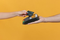 Close up cropped photo of female and male hold wireless modern bank payment terminal to process acquire credit card payments isolated on yellow background. Money, achievement, career wealth concept