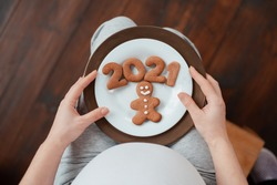close up. Cropped photo of pregnant woman holding number 2021 of ginger cookies twins. people and expectation concept. Happy motherhood, healthy life. expecting children. Baby born in 2021 copyspace