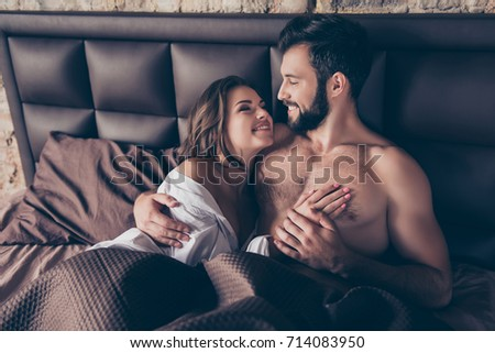 Close up cropped photo of stunning young sexy brunette embracing her lover in bed, he is bearded handsome brunet, smiles, looks at her. Lady is gorgeous and hot #714083950