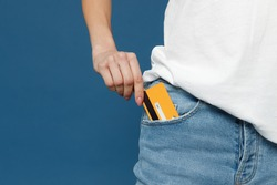 Close up cropped photo portrait shot of caucasian female hand arm putting credit bank card in jeans pants denim pocket isolated on dark blue background studio portrait. Money finance currency concept